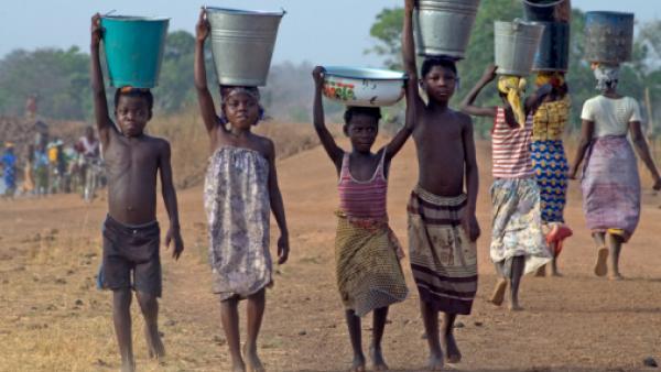 Enfants avec bassines d'eau sur la tête